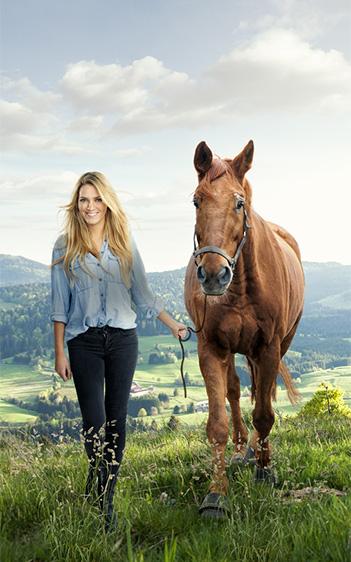 Lächelnde Frau und Pferd spazieren auf sommerlicher Wiese