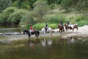 Gemeinsamer Ausritt mit Pferd durch reißende Flüsse – Horsia Ratgeber